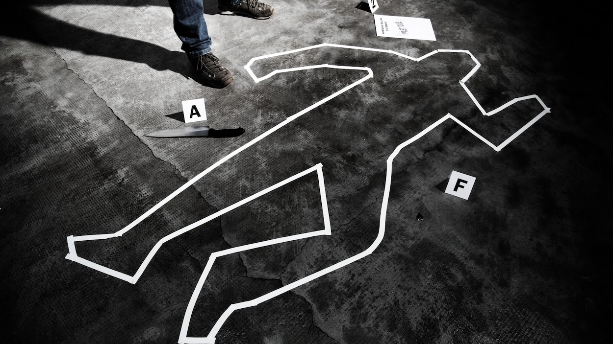 On voit en blanc le tracé d'un corps humain sur une scène de crime reconstituée.