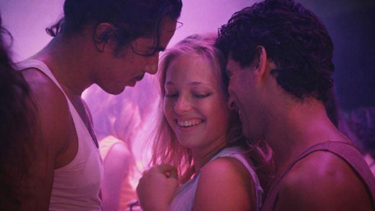 Une femme dans une boîte de nuit danse collée sur deux hommes.