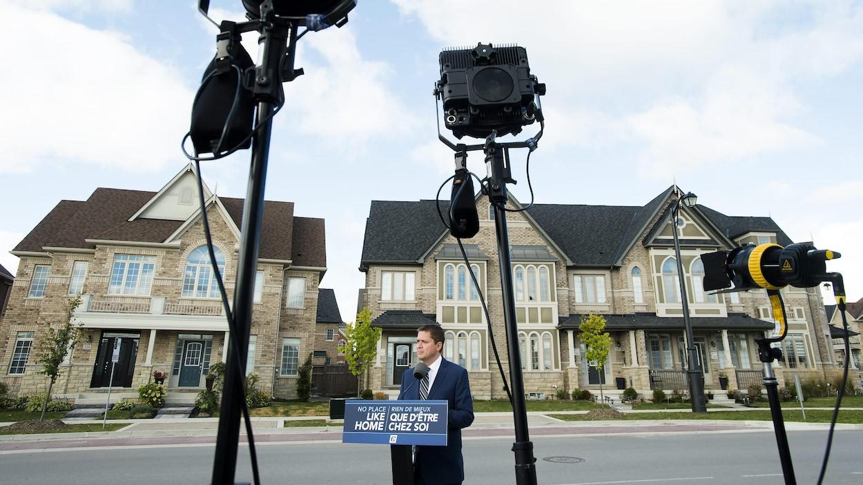 M. Scheer s'adresse aux médias devant des maisons en rangée.