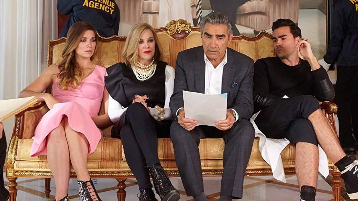 Deux femmes et deux hommes sont assis sur un divan et regardent un document d'un air inquiet.