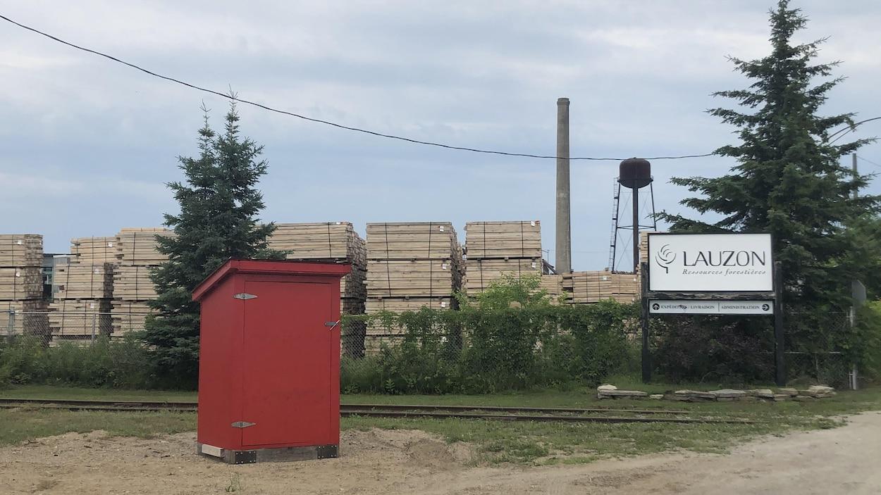 Des planches de bois s'empilent dans la cour de la scierie Lauzon.