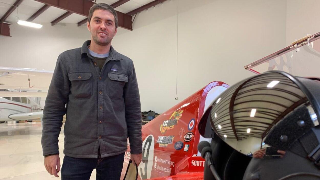 Scott Holmes dans un hangar de l'aéroport de Villeneuve. Il se tient à côté d'un prototype d'avion.