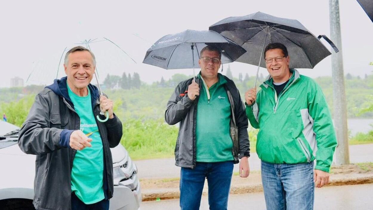 Le premier ministre, Scott Moe, tient un parapluie dans sa main droite et est entouré de deux hommes.