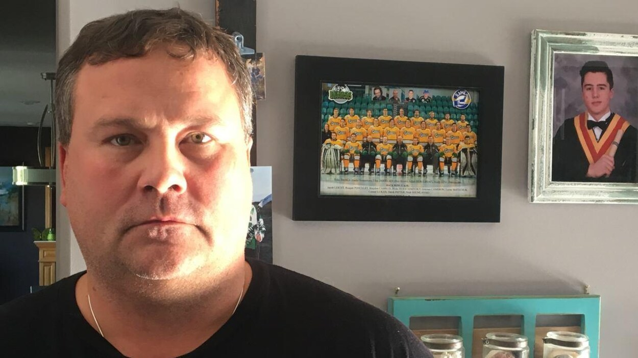 Scott Thomas pose devant le portrait de son fils mort dans l'accident des Broncos en avril 2018.