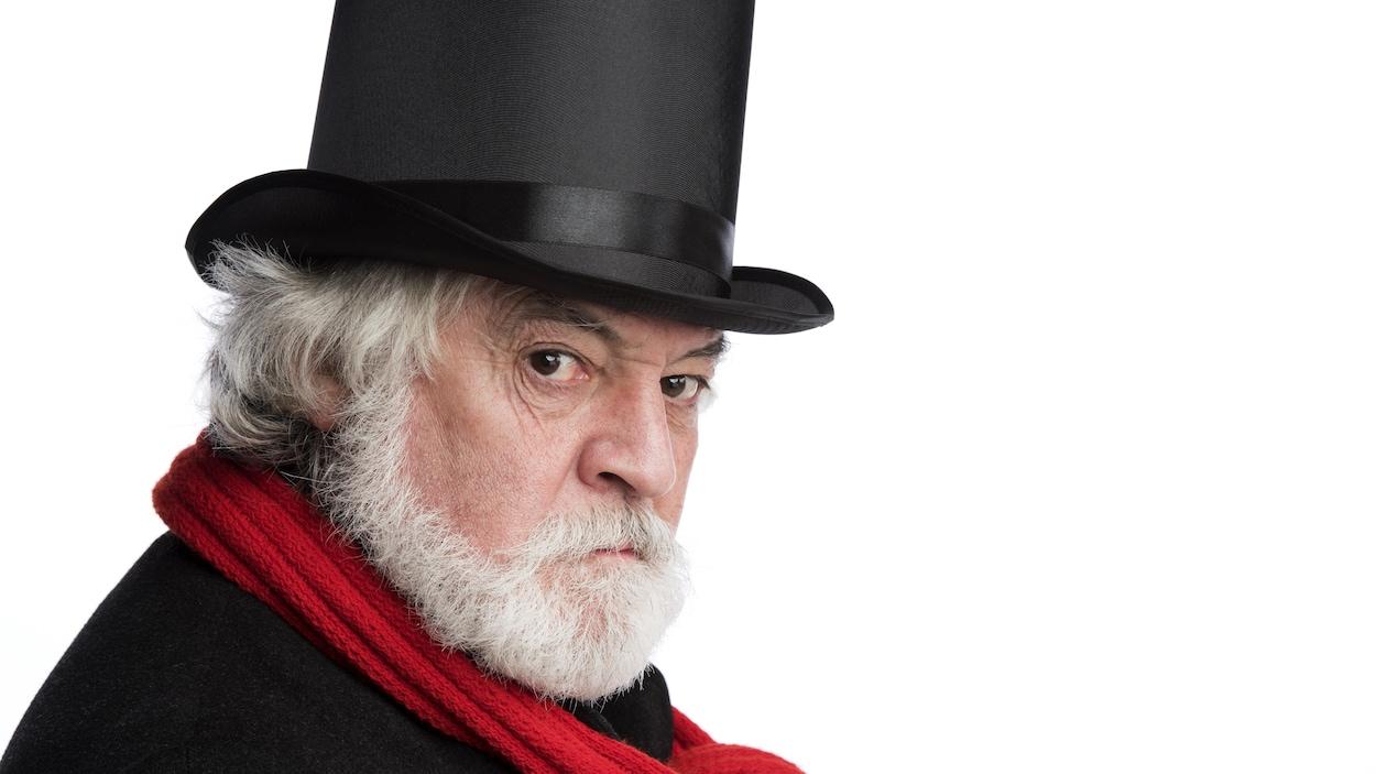Russell Roberts dans le rôle de Scrooge avec son chapeau haute-forme et son foulard rouge au théâtre Gateway à Richmond.