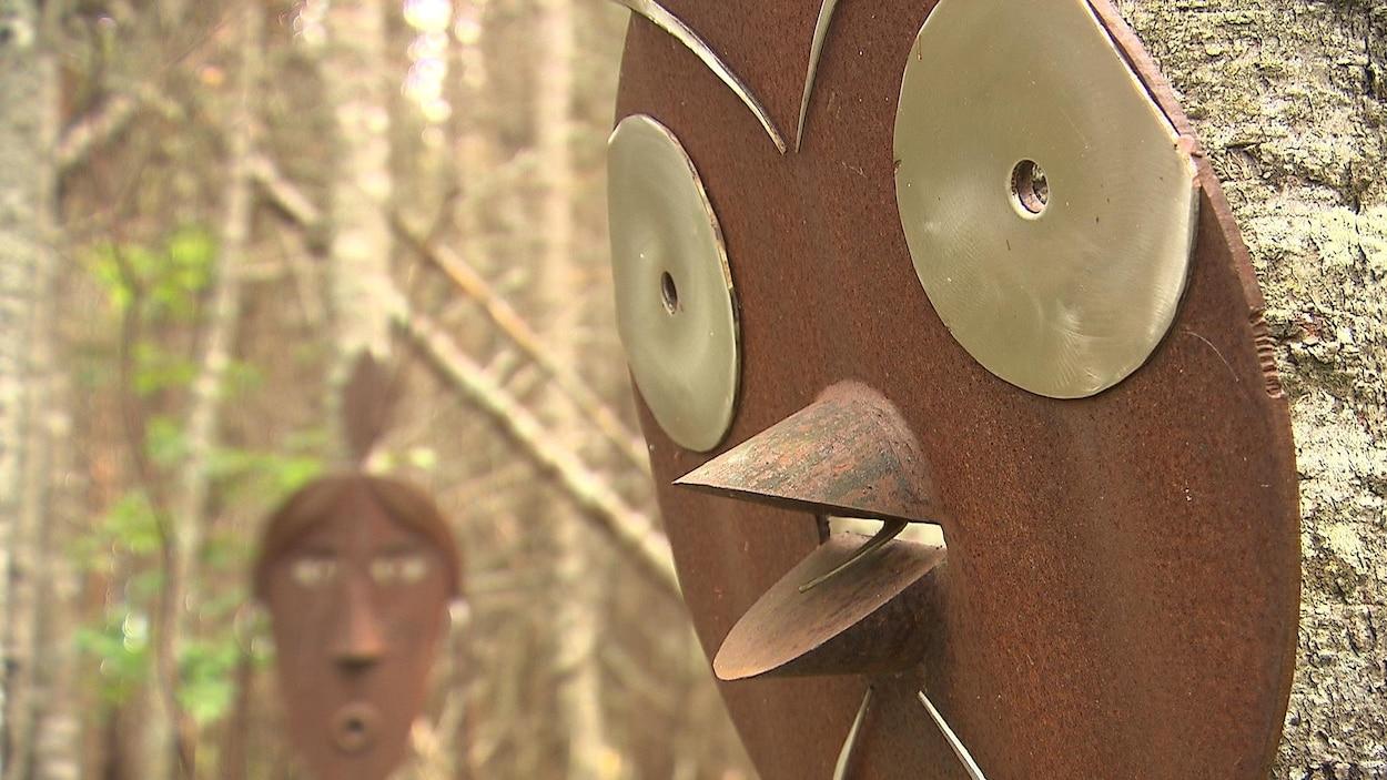 Une sculpture d'oiseau en fer dans une forêt