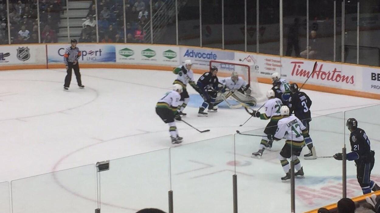Une mêlée de hockeyeurs devant le filet