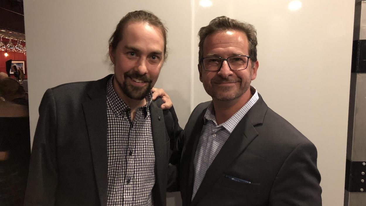Deux hommes sourient à la caméra en se tenant par les épaules.