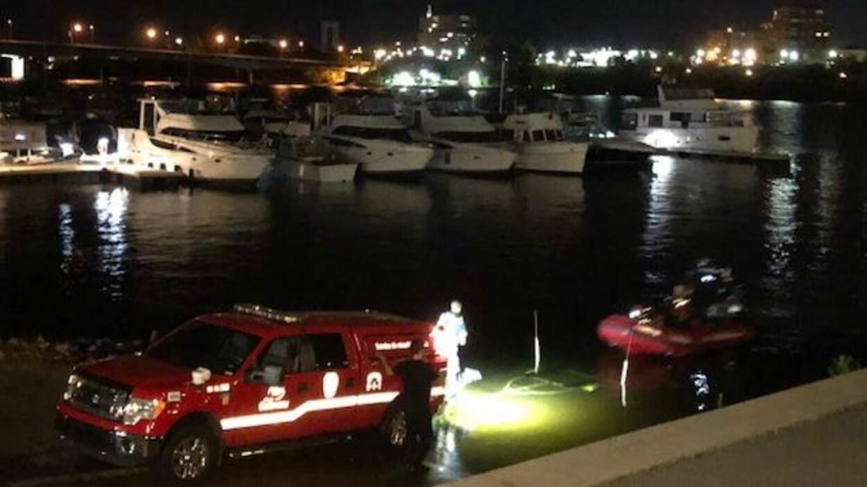 Un bateau pneumatique et une voiture des services d'urgences dans une marina.