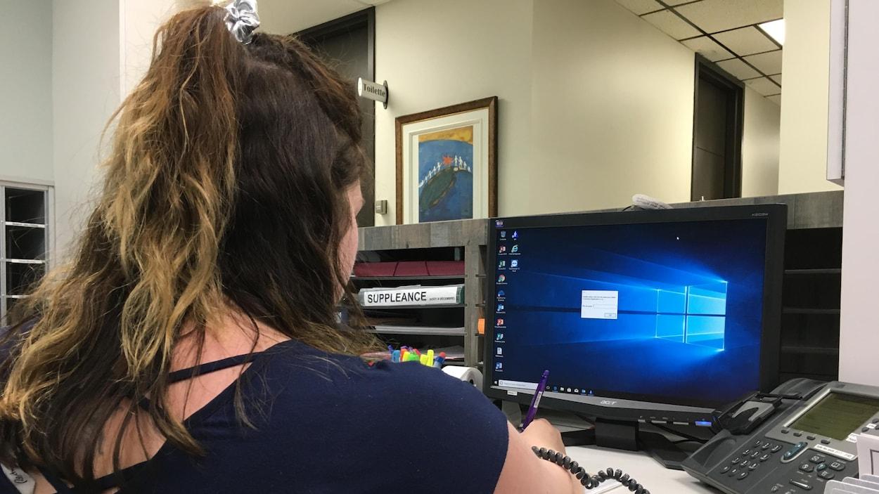 Une secrétaire face à son ordinateur.
