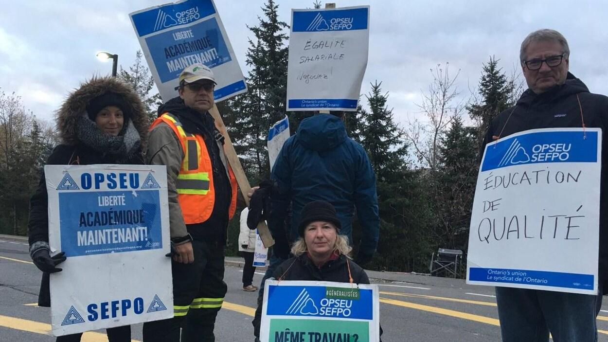 Des grévistes tiennent des pancartes
