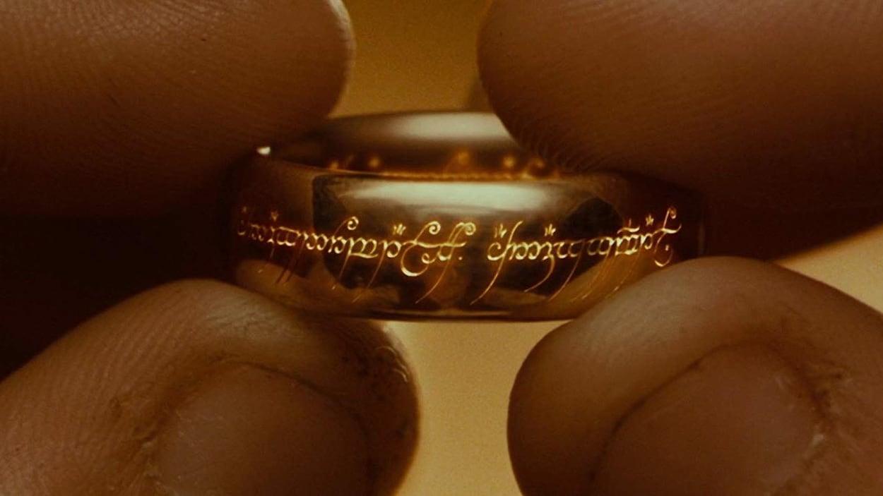 Deux mains tiennent un anneau doré entre leurs doigts.