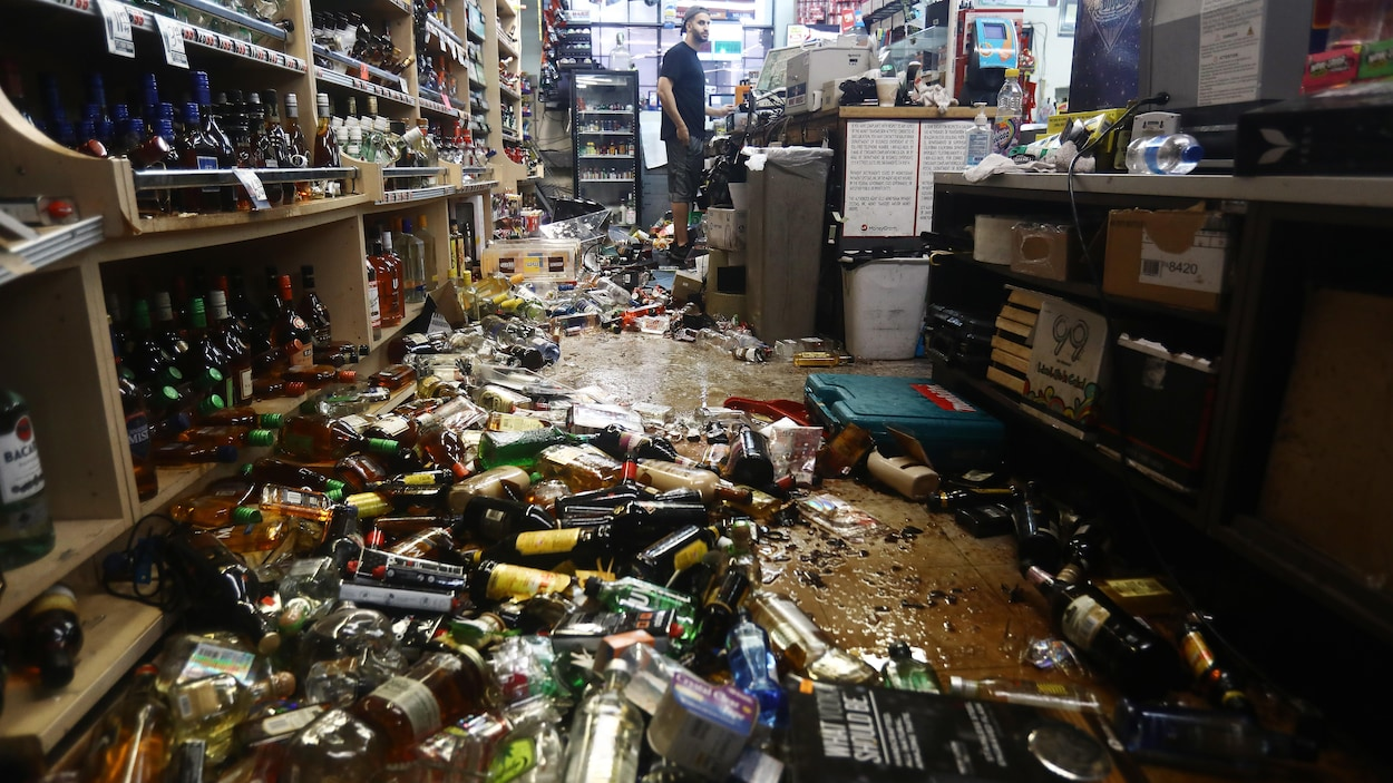 Des bouteilles d'alcool sont écrasées sur le sol d'un magasin.