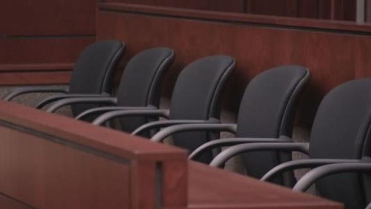 On aperçoit un box de jurés vide dans un tribunal