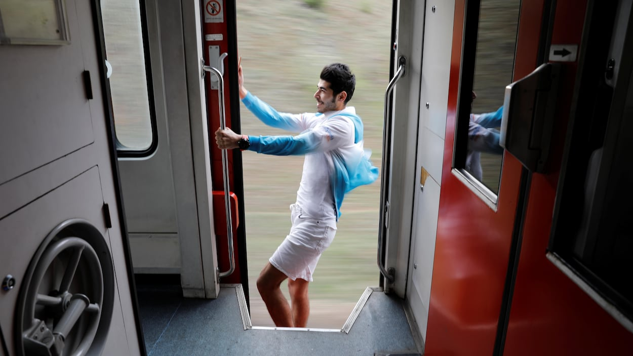 Le jeune homme se tient d'une main à l'extérieur du train en mouvement.