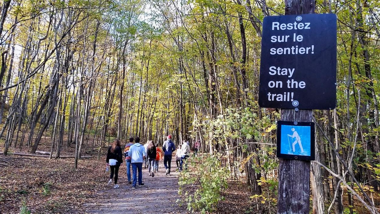 Des randonneurs dans le parc de la Gatineau, à l'automne. Sur une affiche, on peut lire : « Restez sur le sentier! »