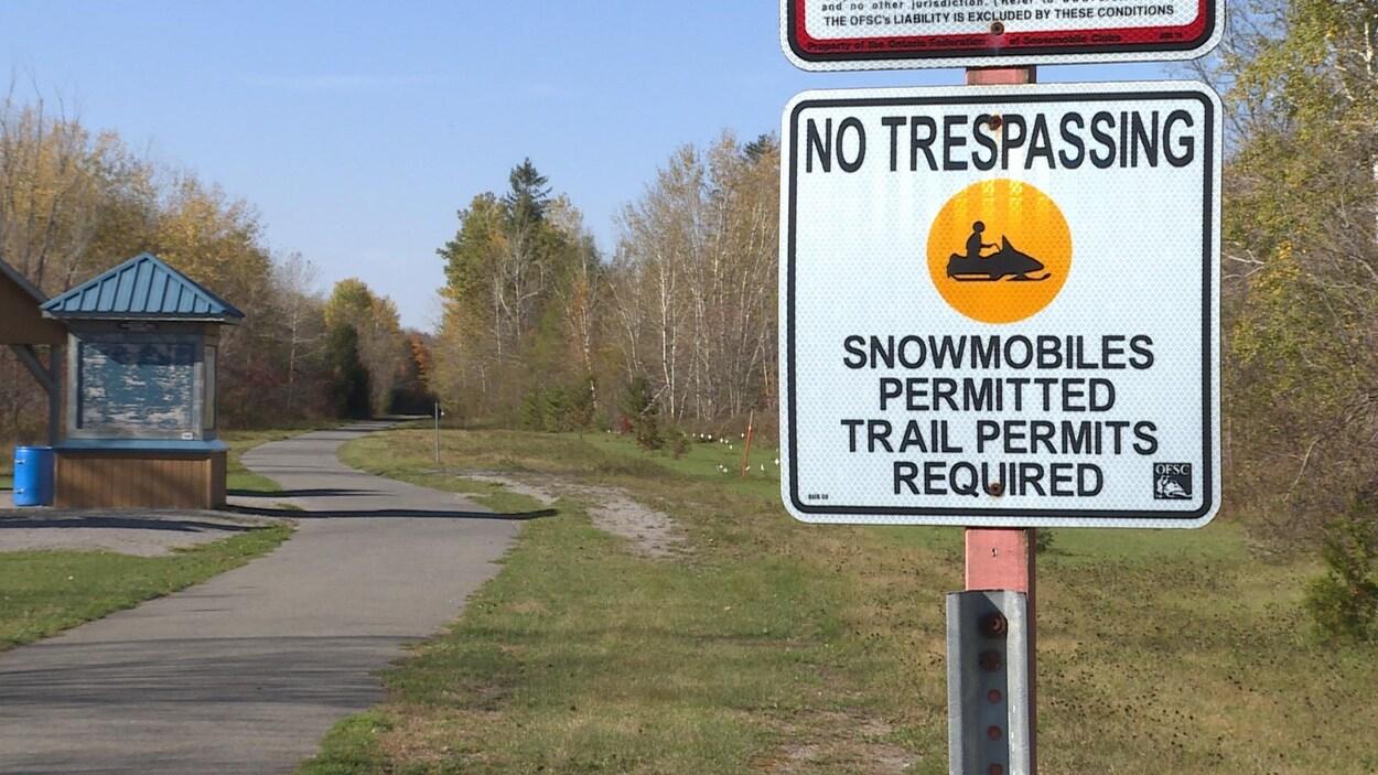 Un panneau de métal sur lequel on peut lire « No Trespassing » à l'entrée d'un sentier boisé.