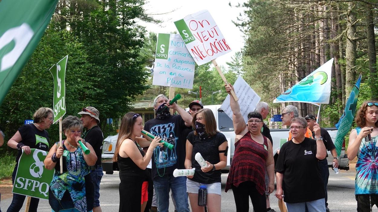 Les travailleurs tiennent des affiches avec des messages comme «On veut négocier» et «Notre confiance a disparu, de la patience on n'en a plus».