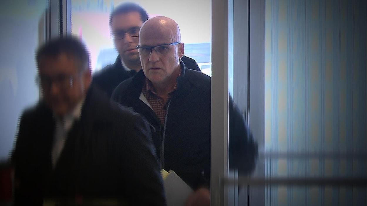Précédé d'un homme et suivi d'un autre, Serge Carré entre à la cour itinérante de Forestville pour sa comparution.