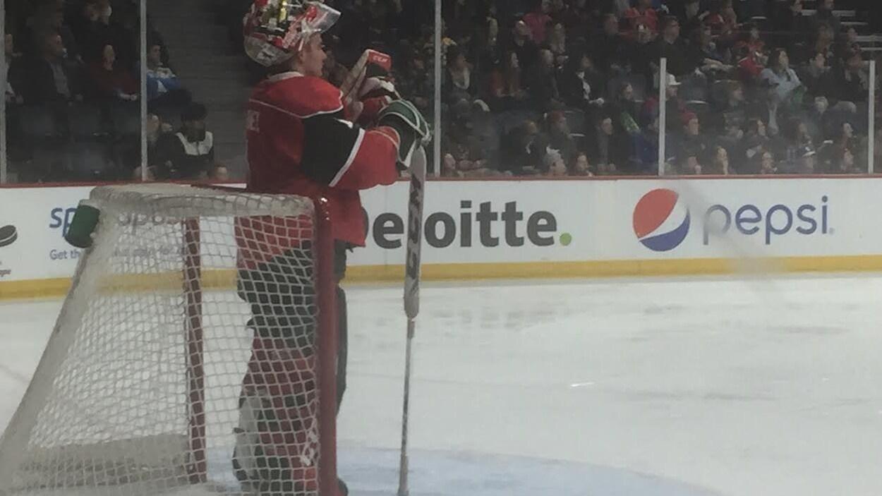 Un gardien de but au hockey s'appuie sur son bâton devant son filet