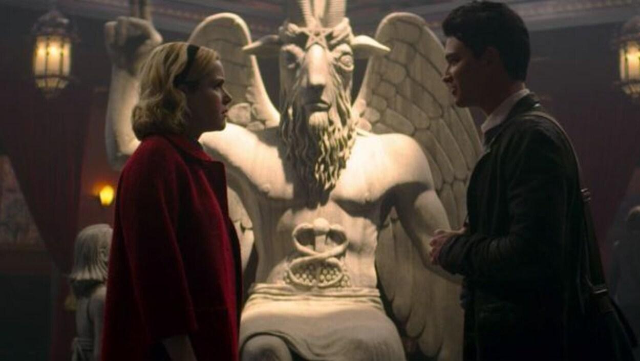 Sabrina, accompagnée d'un jeune homme, se tient debout devant la statue en pierre.
