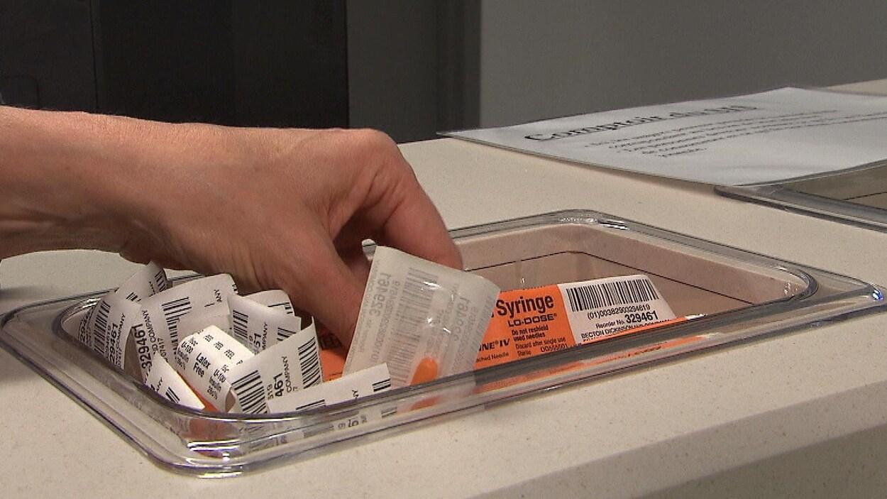 Des seringues dans un bac, dans un centre d'injection supervisée