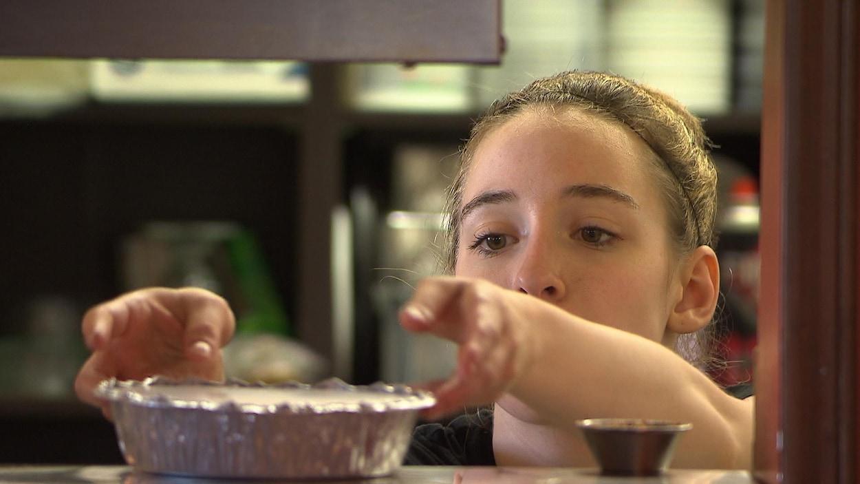 Une serveuse dépose un plat sur le comptoir.