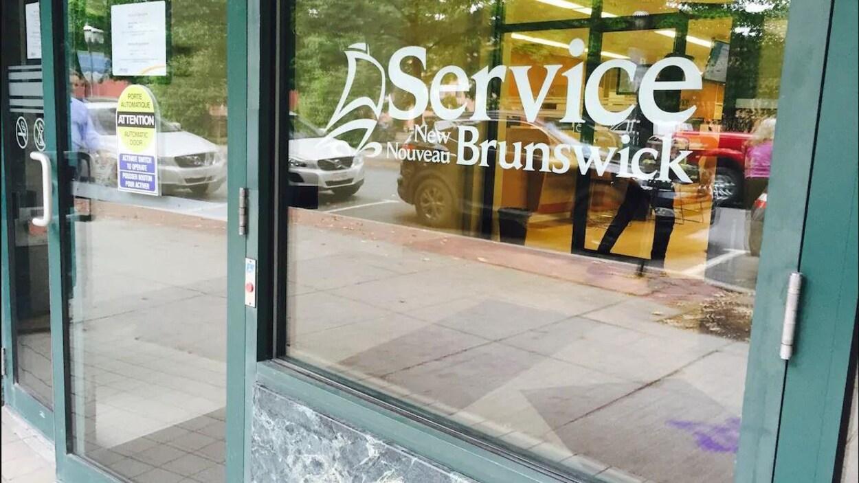 Le logo de Service Nouveau-Brunswick dans une fenêtre de leur bureau.