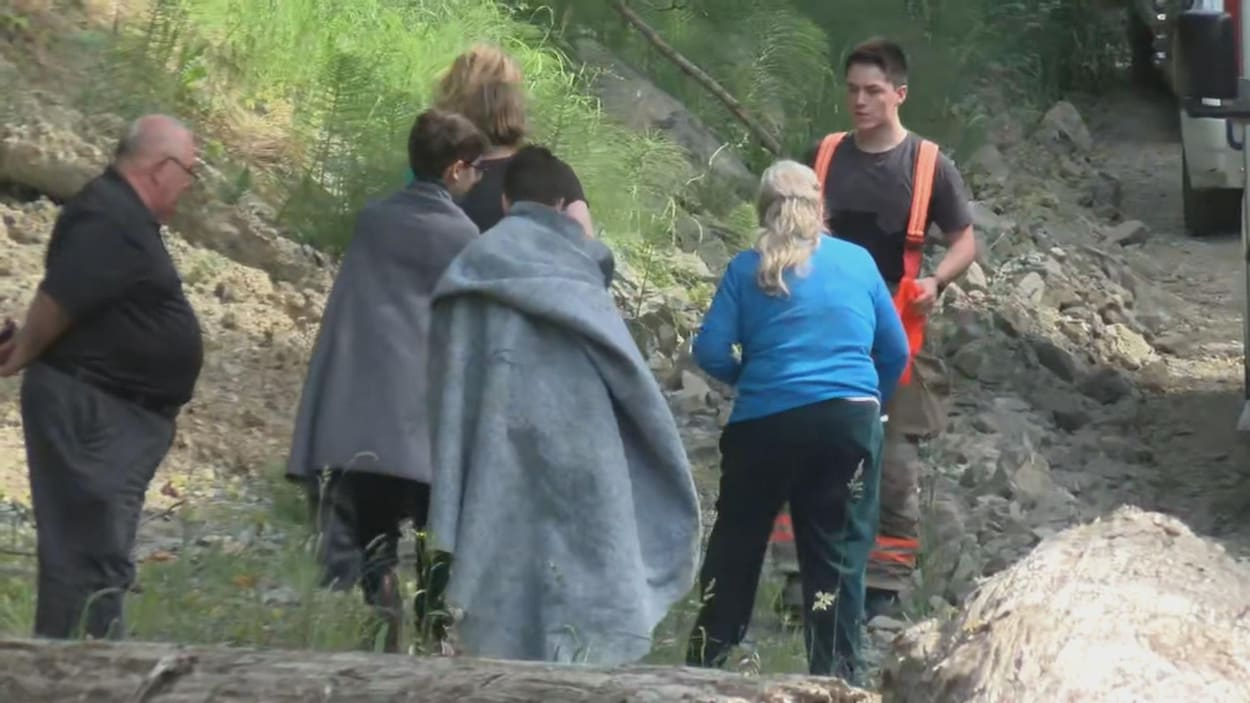 Deux jeunes recouvert de couvertures, trois adultes et un pompier dans la nature.