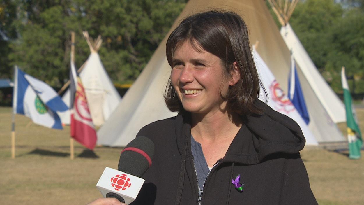 Une jeune femme aux cheveux courts sourit en direction d'une journaliste hors cadre. Derrière elle se trouve le tipi principal, entouré des drapeaux des commaunautés ayant apporté leur soutien au camp.