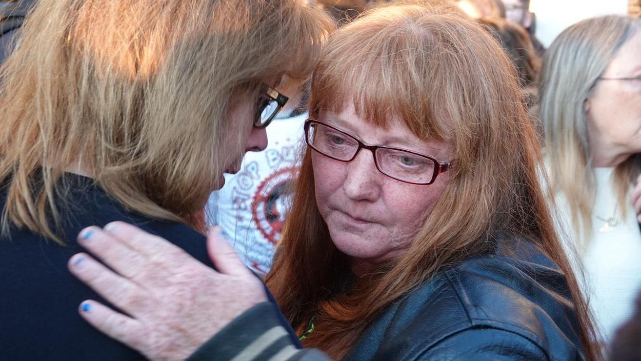 Une femme en pleurs est consolée par une proche.
