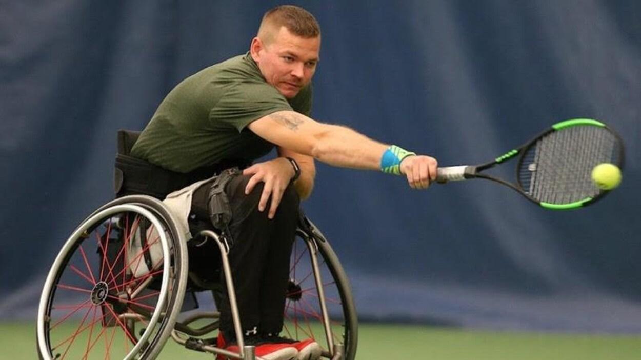 Un homme est assis dans un fauteuil roulant. Il joue au tennis.
