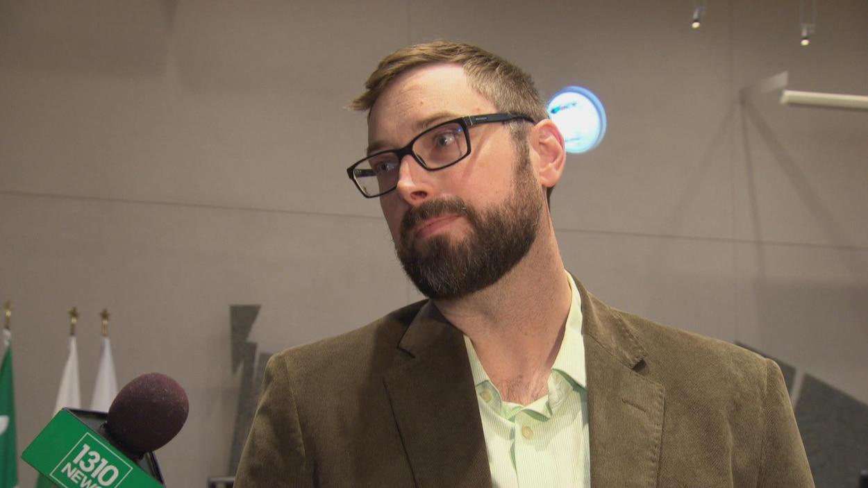 Shawn Menard dans la salle du conseil municipal d'Ottawa. À sa gauche, un micro.