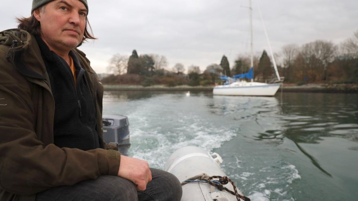 Un homme porte une tuque et un manteau. Il regarde l'horizon en conduisant son bateau.
