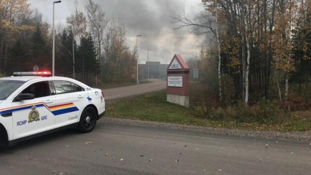 Une voiture de police devant la prison de laquelle s'échappe un énorme panache de fumée