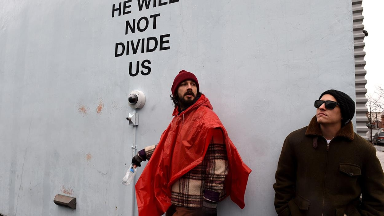 Shia LaBeouf devant l'installation « He Will Not Divide Us » au Museum of the Moving Image à Queens, New York