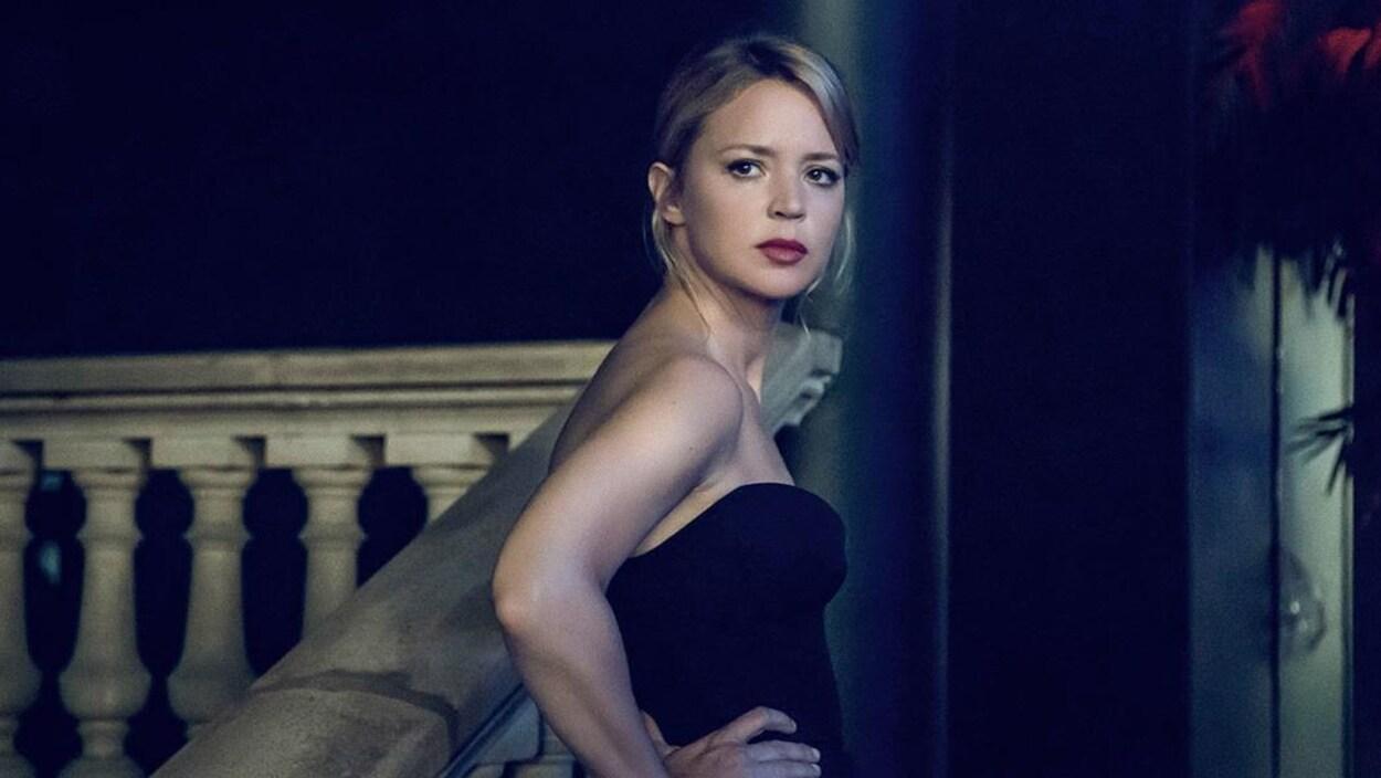 Une femme sur un escalier regarde au loin.