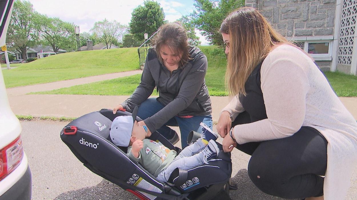 Une bénévole ajuste le siège d'auto d'un enfant devant sa mère.