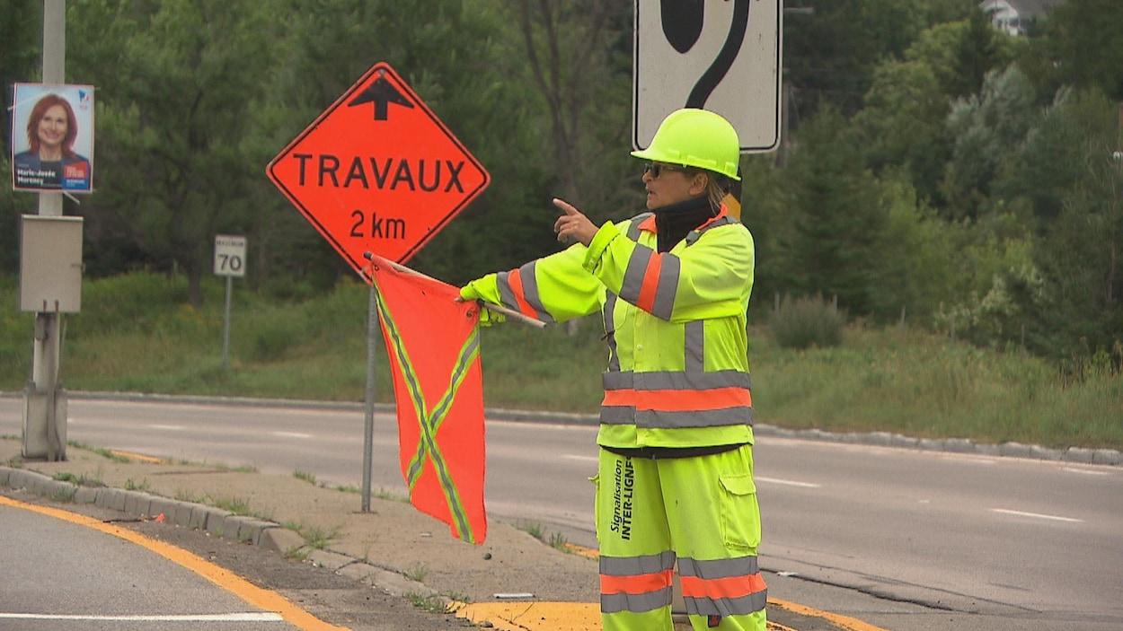 Une femme en habit de sécurité tient un drapeau orange et donne des indications avec sa main.