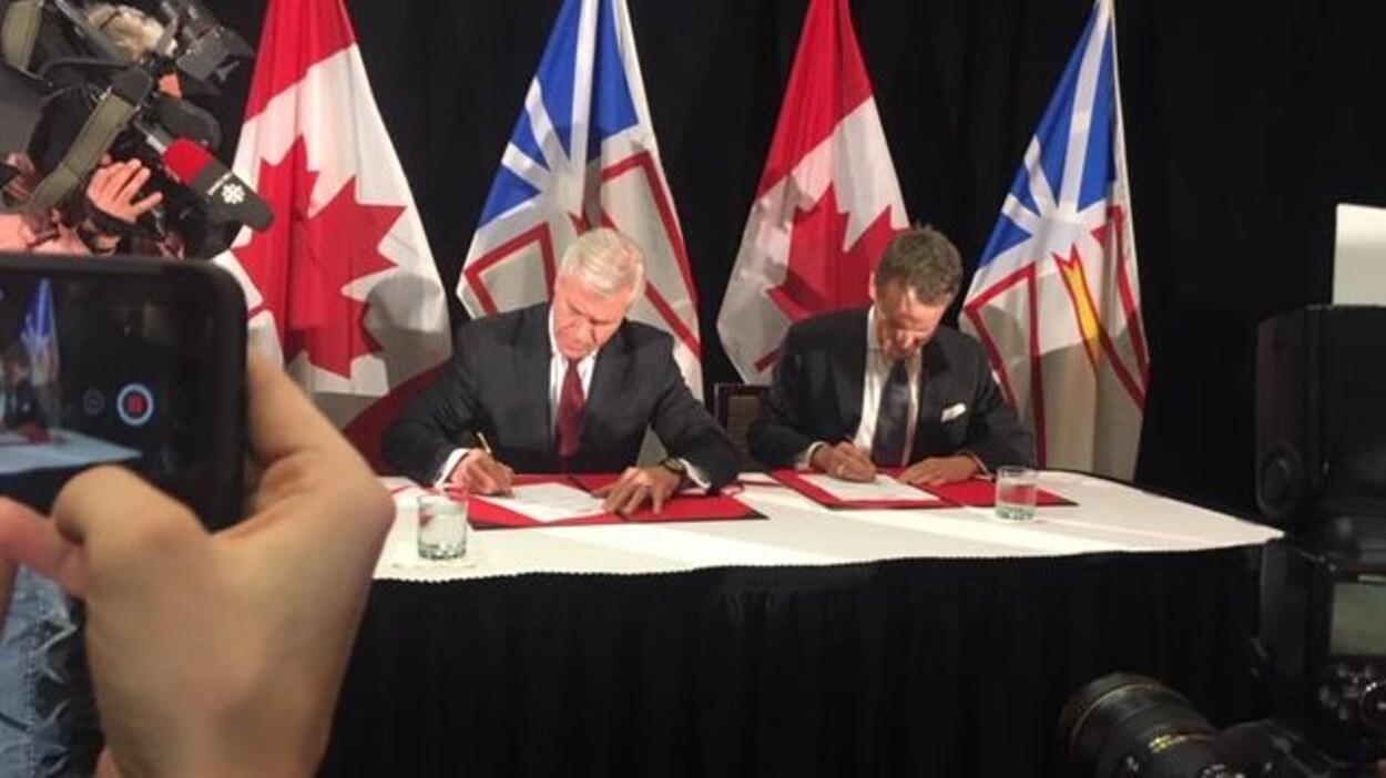 Les deux politiciens en train de signer devant les caméras.