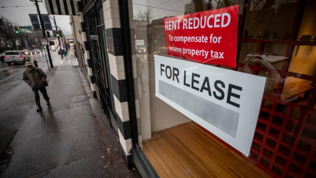Une affiche dans la vitrine d'un local commercial sur laquelle il est inscrit, en anglais : « loyer réduit pour compenser l'impôt foncier démesuré ».