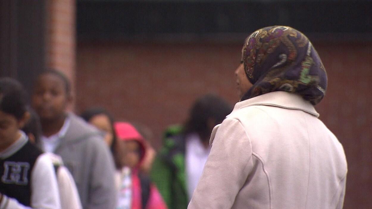 Une femme avec un hidjab dans une cour d'école
