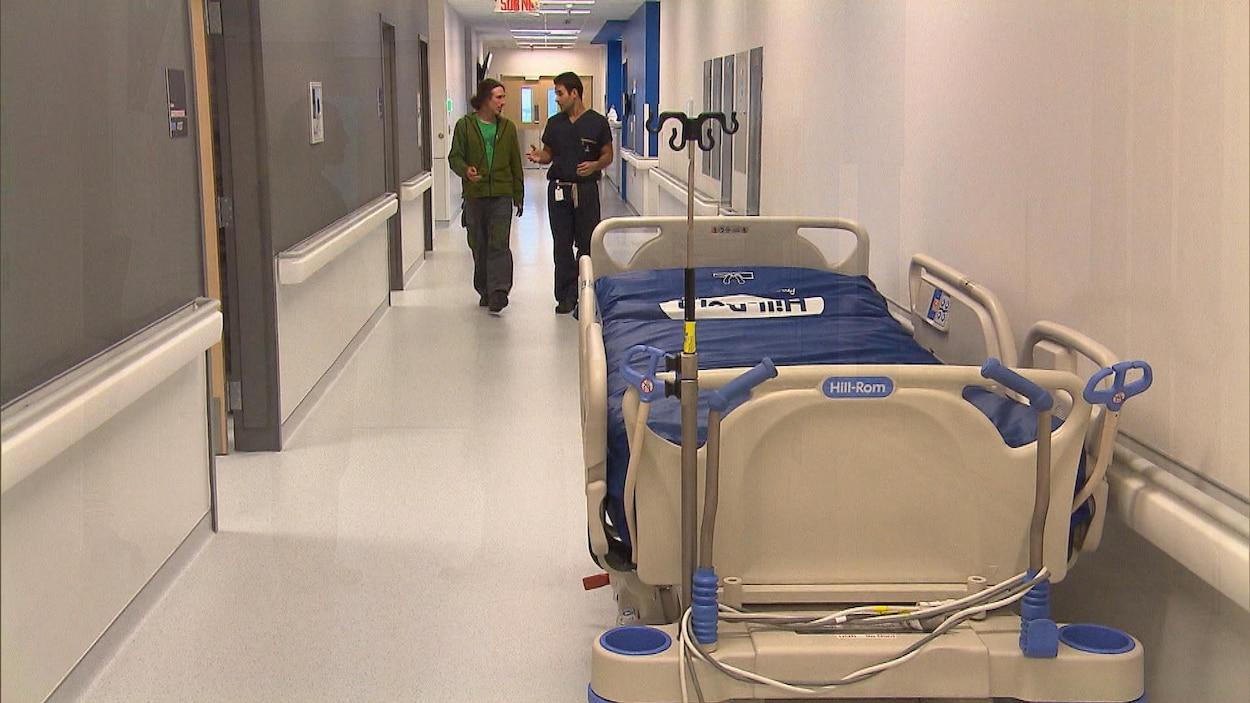 Un patient et son médecin déambulent dans le couloir d'un hôpital où l'on peut voir une civière, vide.