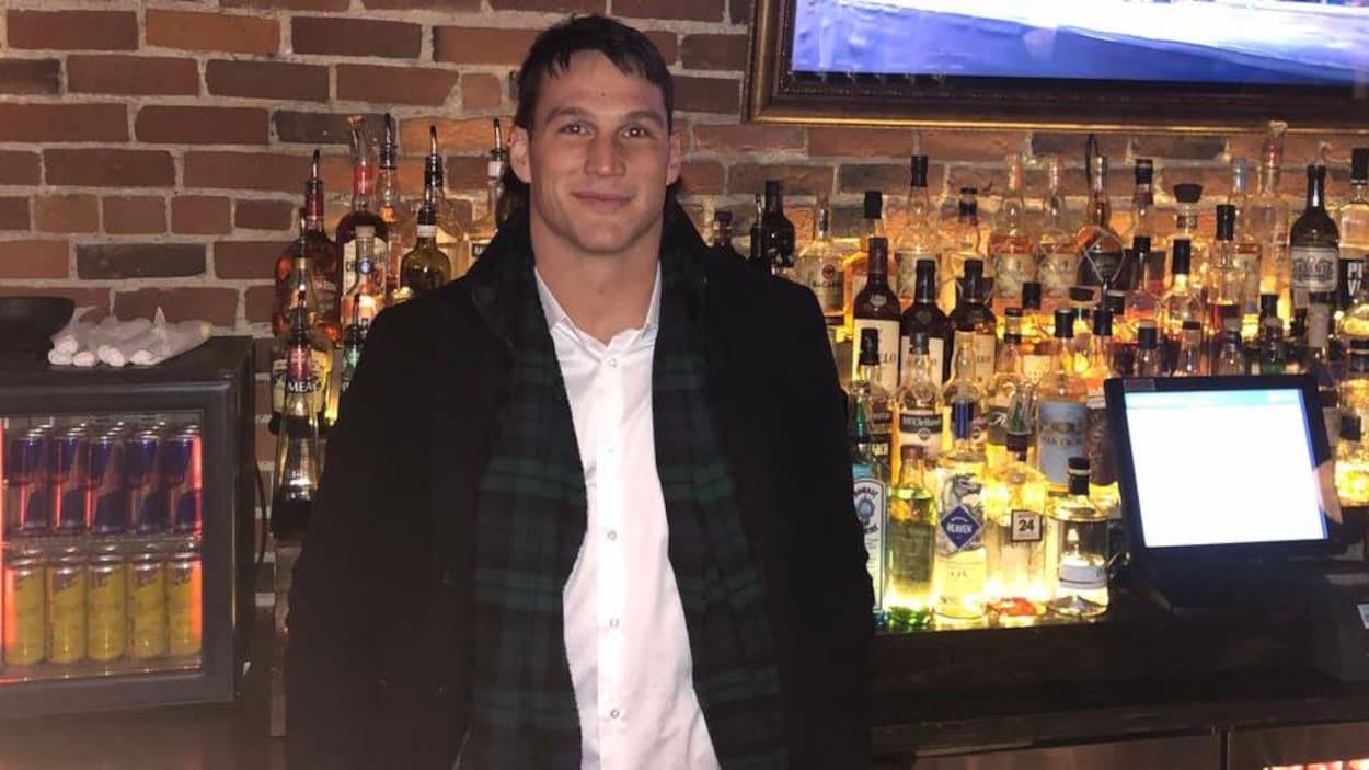 Un homme devant un bar rempli de bouteilles d'alcool.