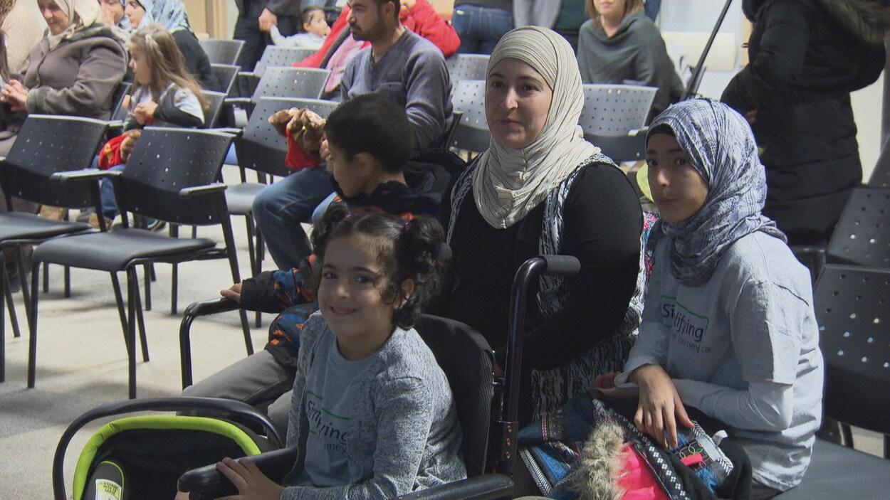 Une femme et des enfants sont assis dans une salle