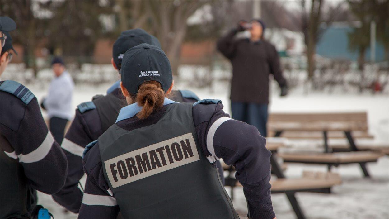 Dans une simulation, trois futurs policiers en formation s'apprêtent à intervenir auprès d'une personne qui boit dans un lieu public.