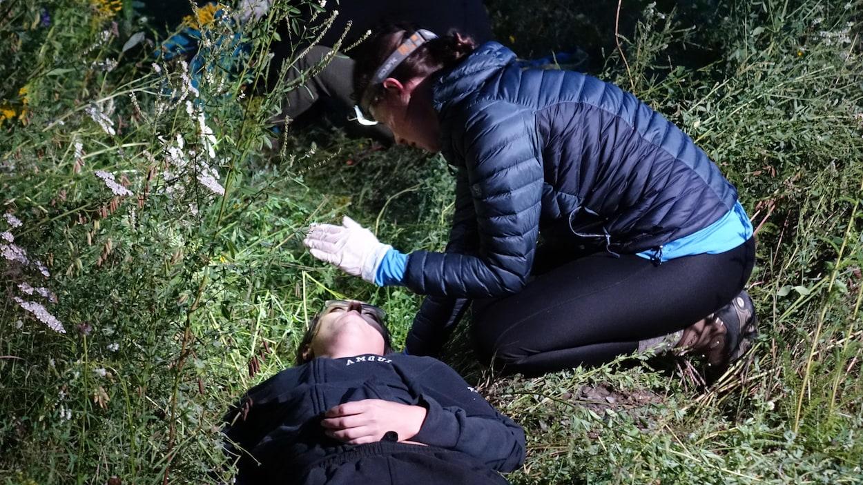 Pendant la simulation, une étudiante évalue une victime.