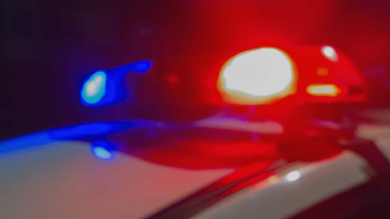 Les gyrophares rouge et bleu d'un véhicule de police dans la nuit.