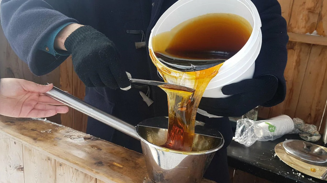 Un homme verse du sirop d'érable dans une casserole.