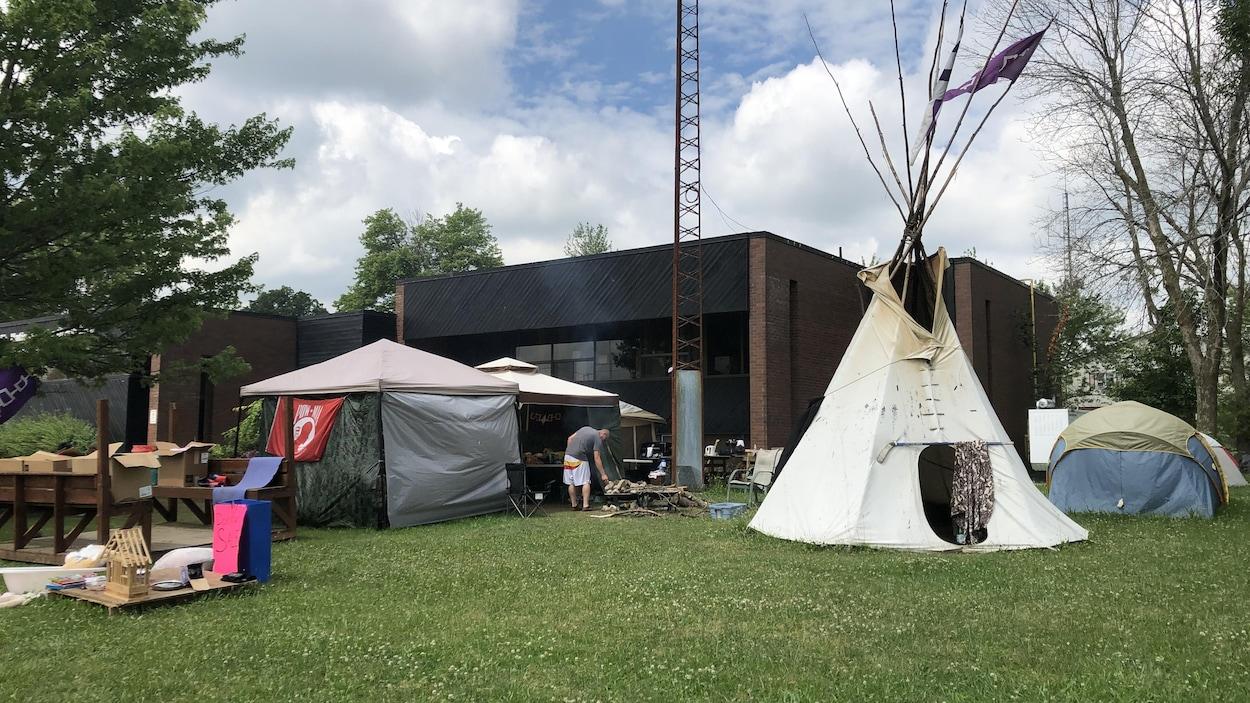 On voit des tentes dont une traditionnelle autochtone devant un bâtiment du conseil de bande.